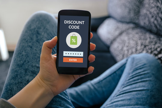 Girl holding smart phone with discount code concept on screen. All screen content is designed by me