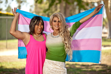 Asian and Hispanic Transgender females smiling proud with pride flag held behind them.