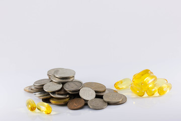 coins and pills on white background. The increase in drug prices