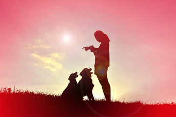 Silhouette women playing with dog