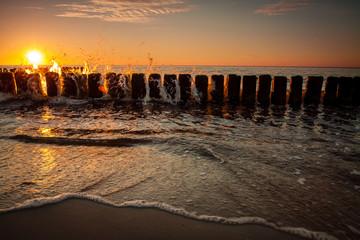 Obraz Zachód słońca nad Morzem Bałtyckim, widok na stare stosy falochronów - fototapety do salonu