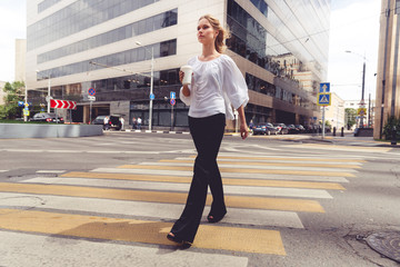 Beautiful blond woman with coffee to go crossing the road