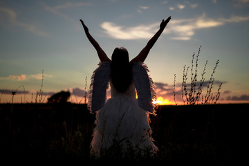 A young woman in the image of the angel stands on a hill with raised hands