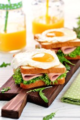 Sandwich with ham, lettuce and a fried egg. Breakfast.
