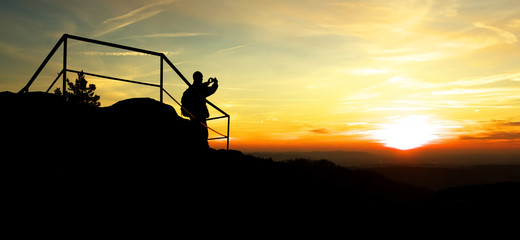 Silhouette of Man Taking Photo of Sunset
