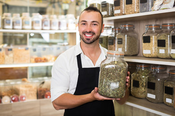 Happy man holding glass can with dried herbs