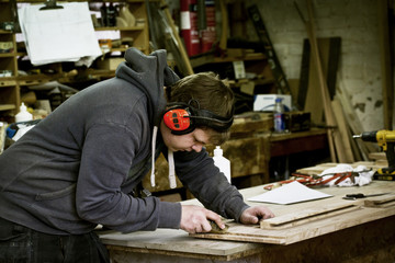 A man working in a furniture maker's workshop wearing ear defenders and using a sharp chisel on wood.