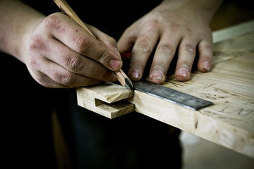 Man working on wood, measuring joint or corner with ruler and pencil