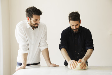 Two bakers standing at a table, kneading bread dough.