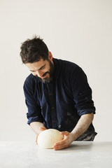 Baker kneading and shaping a portion of bread dough into a ball.