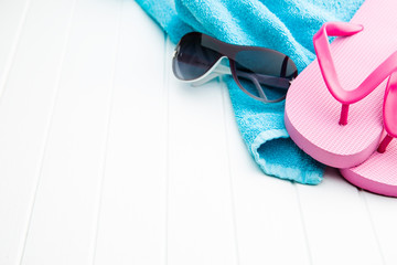 Pink flip flops with towel and sunglasses.