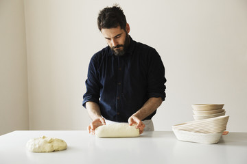 Baker standing at a table, shaping bread dough, a stack of rattan proofing baskets.