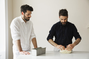 Two bakers standing at a table, kneading bread dough, a metal baking tin.