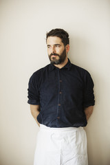 Half length portrait of a bearded man wearing a white apron.