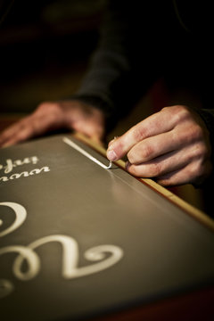 A signwriter working with a loaded brush painting a line freehand on the edge of a sign.