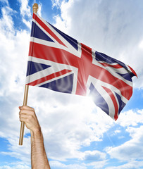 Person's hand holding the British national flag and waving it in the sky, 3D rendering