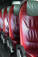 Empty red leather seats in tourist bus.
