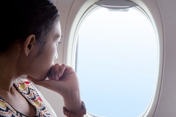 woman looks out the window of an airplane