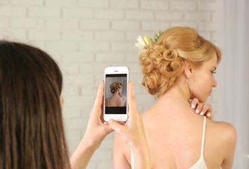 Taking photo of young woman with elegant hairstyle