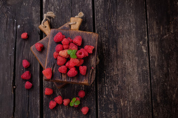 Raspberries on rustic wooden board