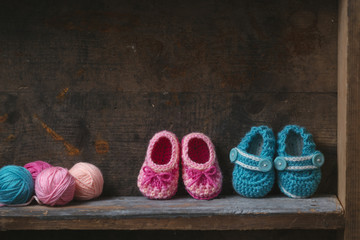 Crochet baby booties with knitting yarn on a wooden shelf.