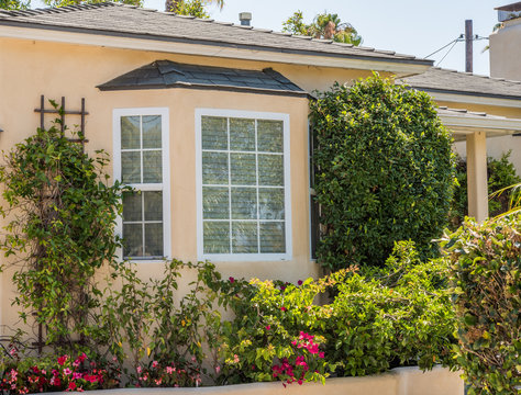 bay window surrounded by flowers and shrubs