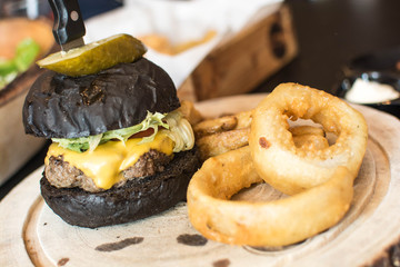 Black burger set on wood dish