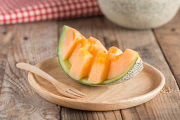 Fresh melon sliced on wood plate.