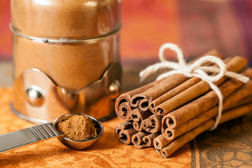 Bundle of cinnamon sticks next to a decorative glass jar and measuring spoon. Close up