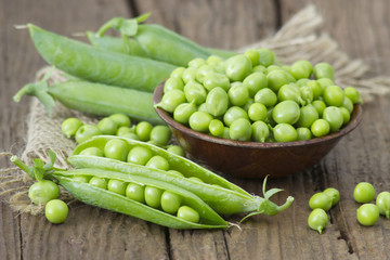 a bowl full of green peas on wooden background