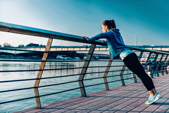 City exercise. Young woman doing standing pushups by the river