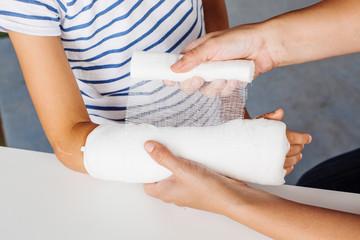 doctor bandaging hand of little patient.