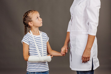 doctor pediatrician holds the hand of a  small girl patient