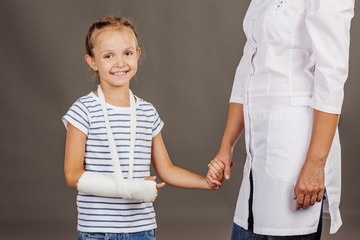 doctor pediatrician holds the hand of a  small girl patient .