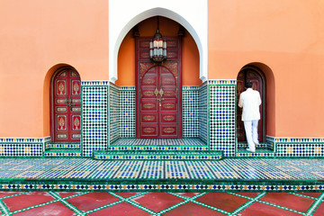 Moroccan building exterior with traditional tile, decorative paint and arched doors