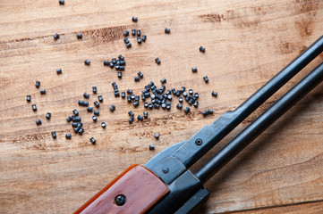 Air rifle and pellet on a wooden background