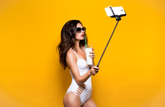 Beautiful brunette model in sunglasses and white monokini taking selfie with cell on selfiestick while drinking cocktail. Studio shot