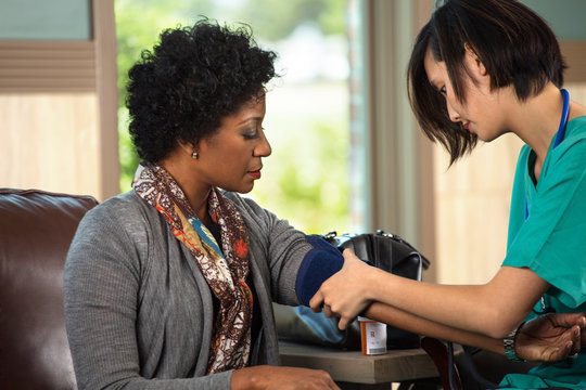 Nurse checking a patients blood pressure.