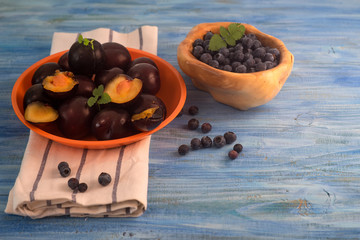 Plum and blueberry on vintage blue wooden table