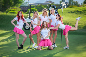 Group of young golf caddies hanging out on golf course with club