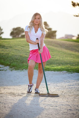 Female golfer caddy raking sand on golf course with copy space.