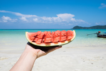 Hand holding watermelon in lipe sea with longtail boat