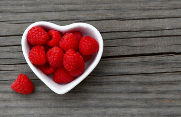 Fresh organic ripe raspberry in a white heart shaped bowl on old wooden background. Selective focus.Healthy food or diet concept.