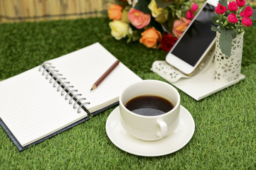 Writing on copy space note book on green grass Background.With s
