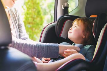 Toddler girl in her car seat Wall mural