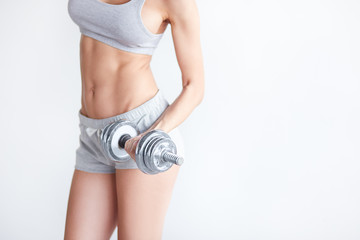 Strong fit woman exercising with iron dumbbell