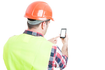 Backview of male engineer holding mobile phone