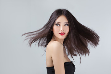 Fashion model with hair blowing in the wind in studio