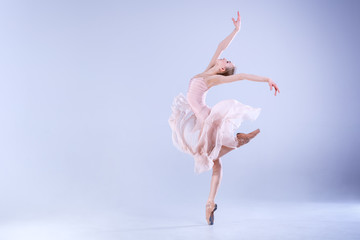 Ballet Perfection. Young and beautiful ballerina is dancing in a white studio full of light.