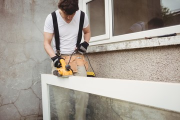 Carpenter polishing a wooden frame